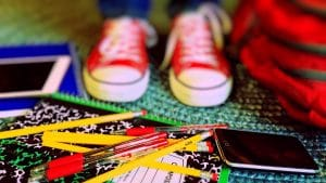 close up shot of kid's Chucks standing among school supplies