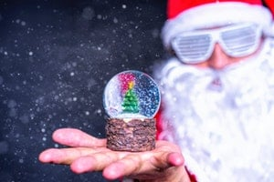 Snowglobe in hand in foreground, out of focus Santa in shutter shades in background