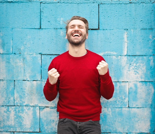 Man in red sweater looking jubilant in front of blue wall