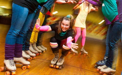 Happy woman skating through line of party guests