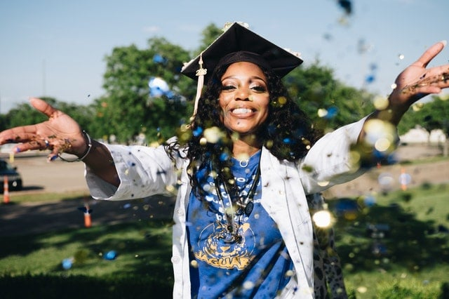 Happy young woman in graduation cap throwing blue and gold confetti