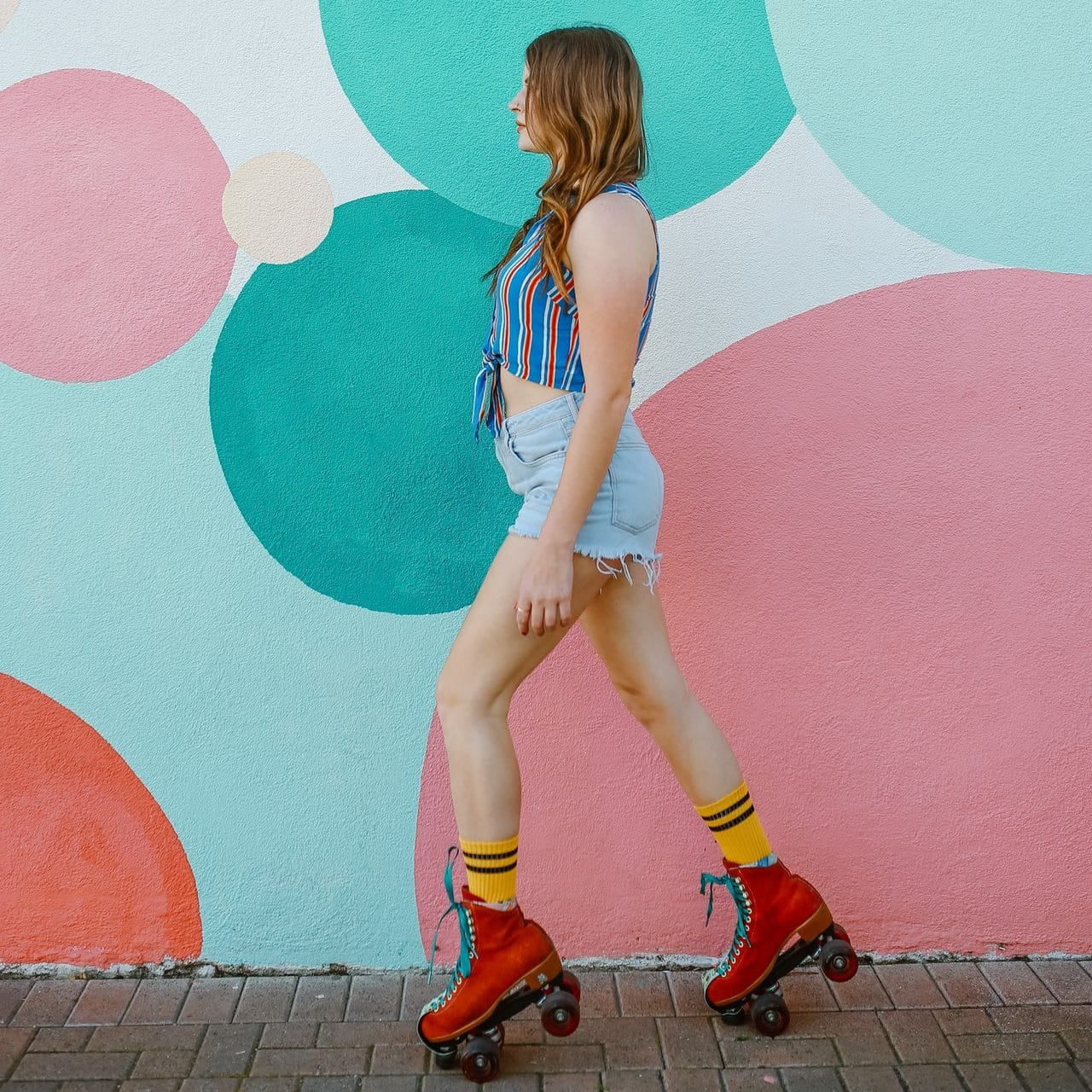 Woman in trendy roller skates in front of street art mural