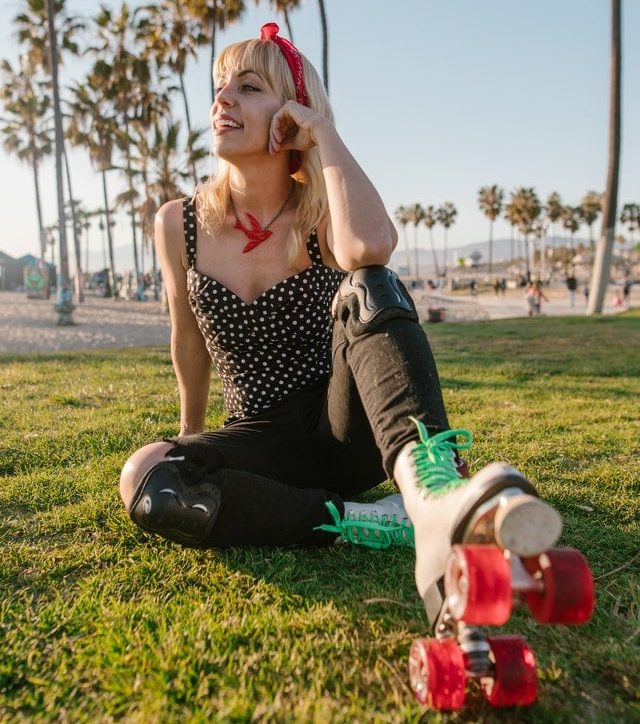 Woman in cute retro outfit wearing roller skates sitting on grass in front of palm trees